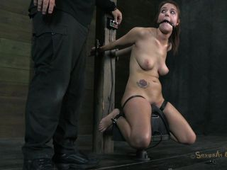 With her hands stuck in metal bars and her thighs tied the brunette is on her knees and receives a deep mouth fuck from her executor. He sticks his dick deep in her throat and continues fucking her although she's suffocating with his penis. Maybe he will cum on her cute small tits at the end!