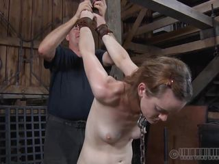 Cute Hazel is tied and hanged by her arms. She has a metal collar around her neck that keeps her head up while her pussy slides on the edge of that board. The pale and fragile chick has a lot to endure and perhaps the harsh punishment she receives will make her be more submissive in her every day life