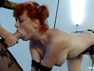 Audrey Hollander is a red haired milf craving for some cock. The bound woman loves having electrodes attached all over her sexy body. Knowing how to treat an obeying sex slave, the hot brunette with big tits and a round ass puts a strapon around her waist and starts to fuck that pink pussy roughly.