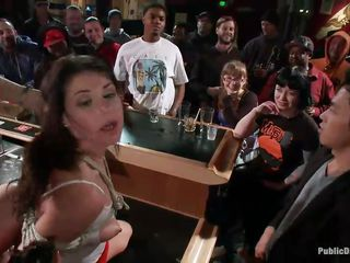 It's a live show in this pub and the crowd is happy with what's going on. A petite brunette is tied with her hands at her back and another slut fists her ass from behind while a guy mouth fucks her. The brutality and intensity of the fuck and the humiliation in public makes everybody feel good and enjoy the show!